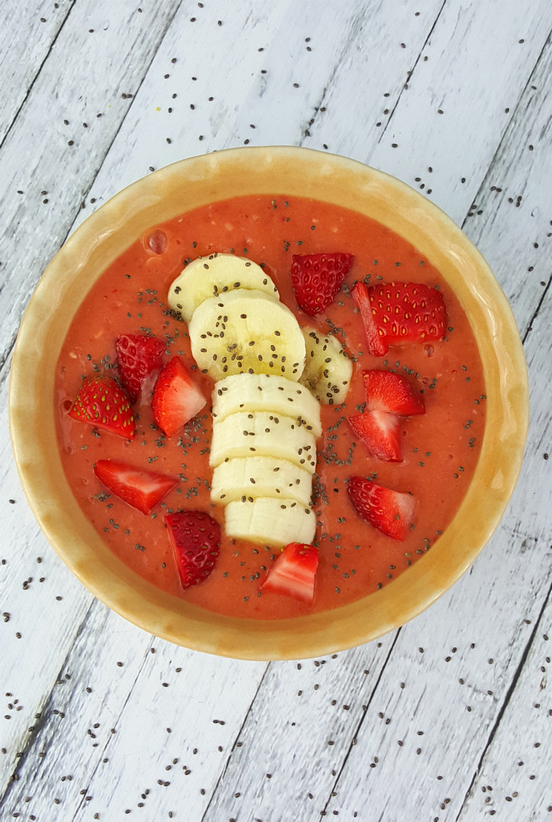 A smoothie bowl served in a yellow bowl with sliced bananas, chopped strawberries and chia seed