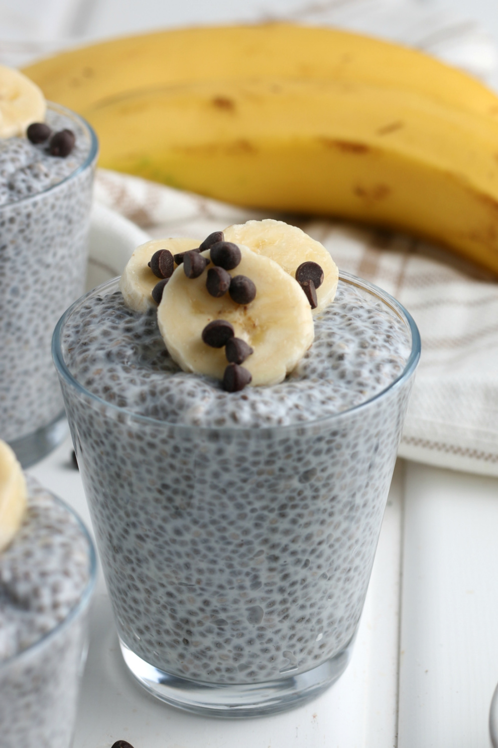 A cup of chia pudding, topped with sliced bananas and chocolate chip