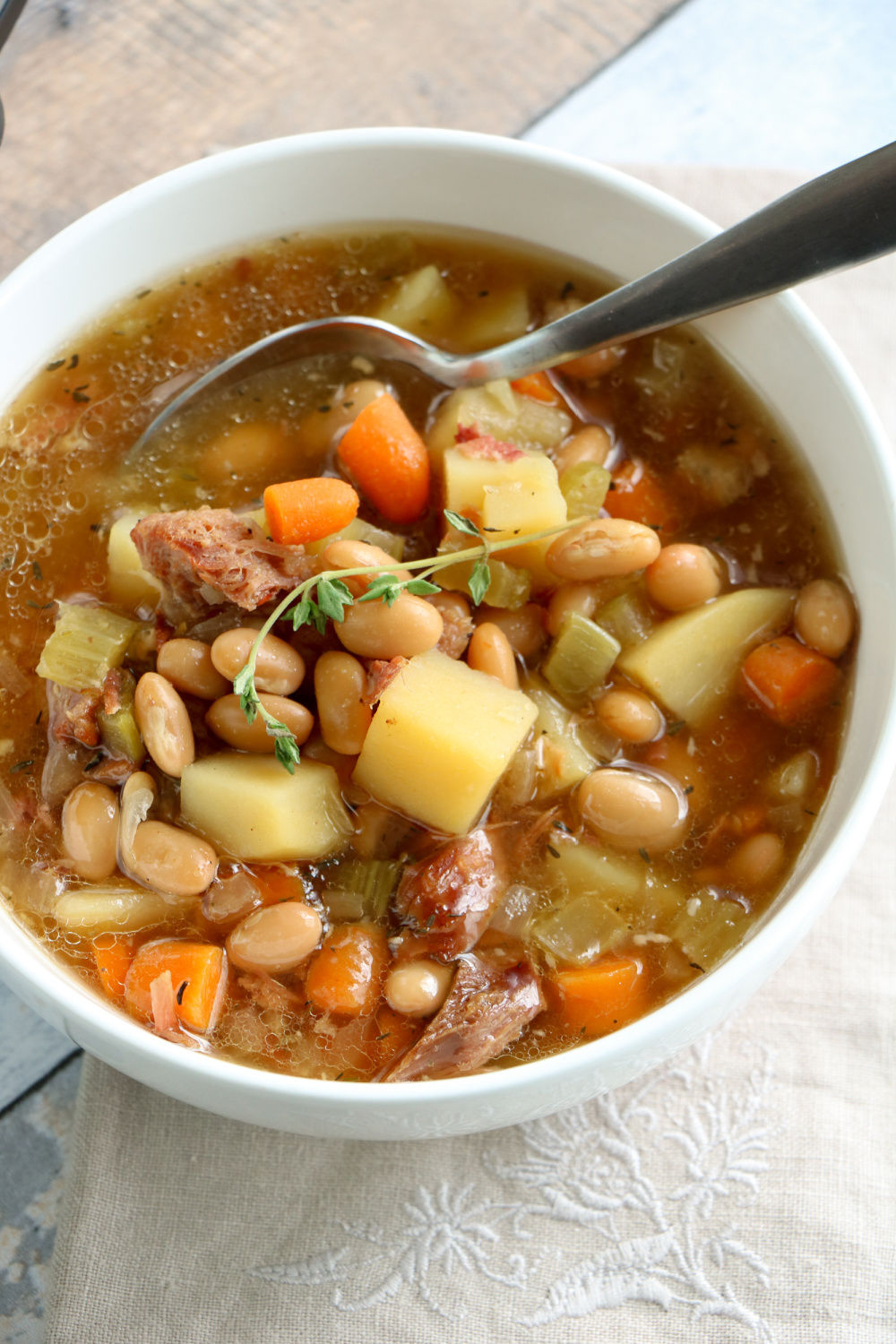 ham bone soup in a white bowl with a spoon
