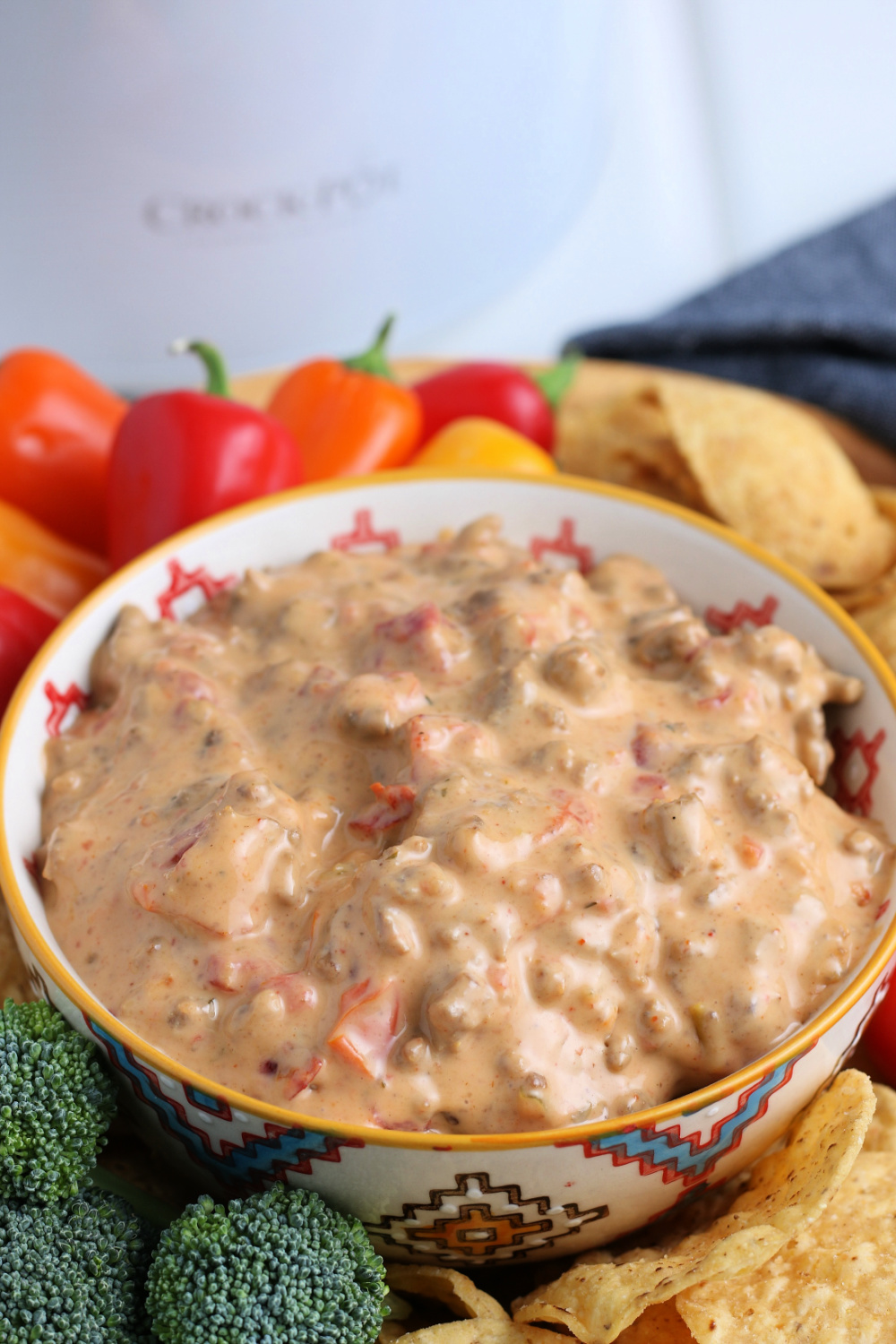 Crockpot Cheesy Rotel Dip in a bowl surrounded by chips and vegetables