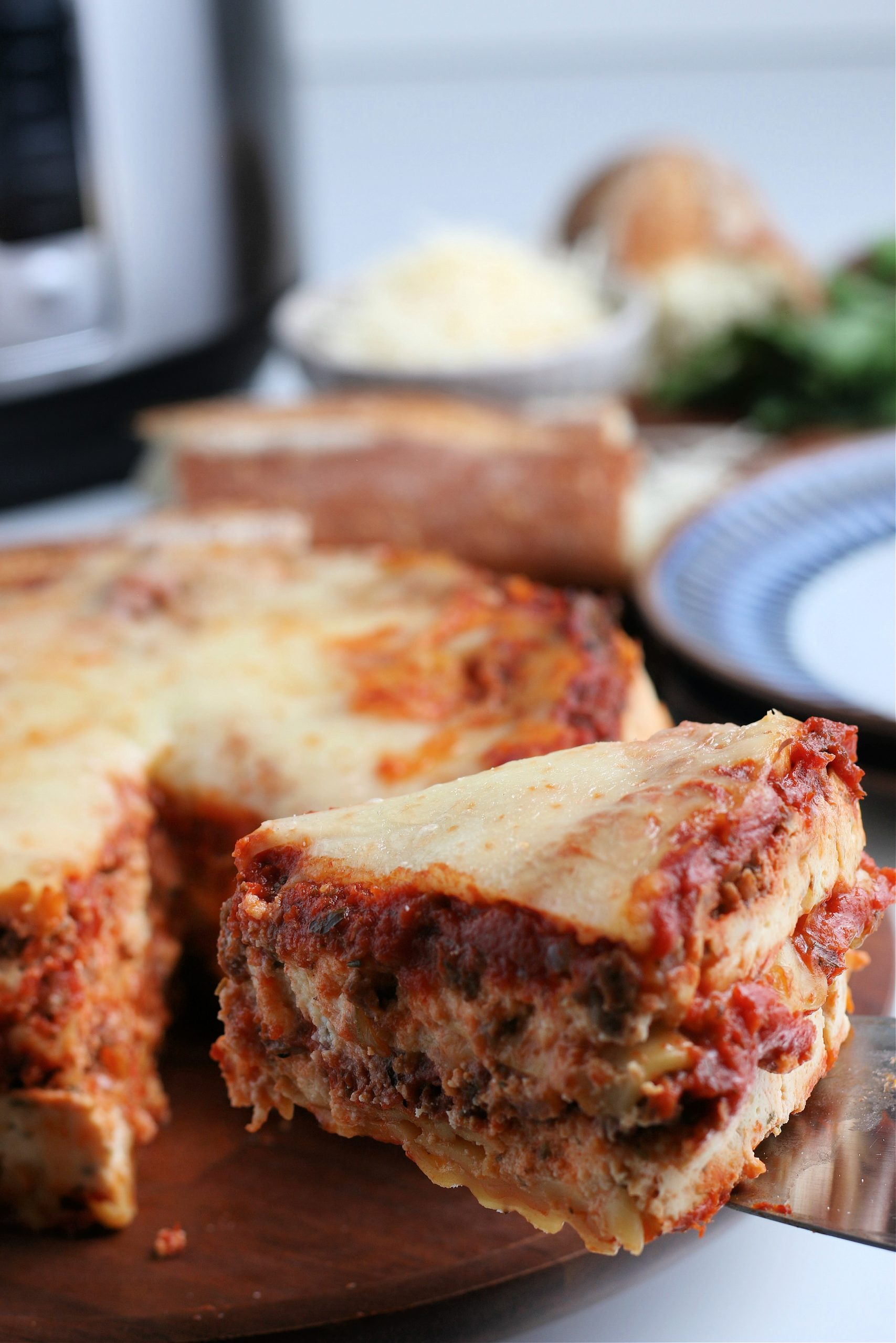 slice of instant pot easy lasagna being held with a serving spatula